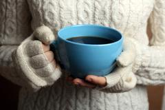 Hot cup of coffee in the women's hands Stock Photos