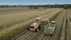 4K Aerial: Behind Tracking Silage Harvester Stock Footage