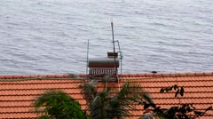 Solar water heating unit boiler on orange tiled roof showing the top of the roof Stock Footage