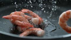 Shrimp splashing into hot oil in frying pan, slow motion; shot on Phantom Flex Stock Footage