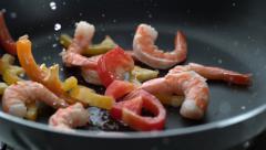 Stir fry splashing into hot oil in frying pan, slow motion; shot on Phantom Flex - stock footage