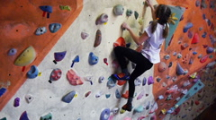 Child climbing on artificial boulders in gym Stock Footage