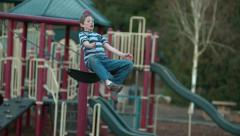 Boy jumping off swing in slow motion; shot on Phantom Flex 4K at 500 fps Stock Footage