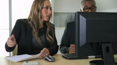 Businessman and businesswoman working together on computer in office - stock footage
