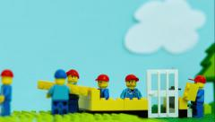 Team of workman Lego mini figure build a house in stop motion. Stock Footage