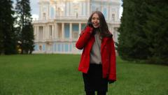 Beautiful girl in warm clothes talking on the phone in park next to old palace Stock Footage