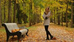 Stock Video Footage of Young sad woman in autumn park (feel cold, cough and try to keep warm).
