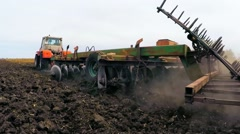 Stock Video Footage of Rural Tractor Trailer Cultivating Soil Of Agricultural Field
