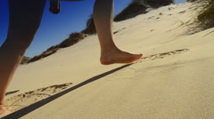 Woman feet climb a dune made of fine sand Stock Footage