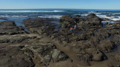 Aerial shot of family on rocks looking in tide pools - stock footage
