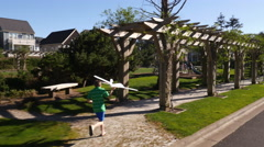 Boy running through park with toy airplane Stock Footage
