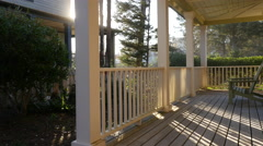 Sunlight shines through railings on beach house porch Stock Footage