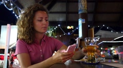 Woman Texting on Phone Drinking Beer in Bar Stock Footage