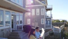 Couple look out from balcony to view of ocean - stock footage