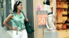 Woman standing and looking on the shop window, steadycam shot Stock Footage