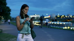 Woman standing on pathway at night and using smartphone, steadycam shot Stock Footage