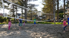Family playing at sand volleyball court Stock Footage