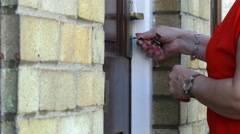 Woman opens two locks on front door. Stock Footage