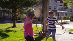 Girls playing with hula hoops at park Stock Footage
