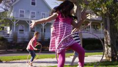 Girls playing with hula hoops at park - stock footage