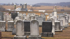 An establishing shot of an Amish graveyard in Pennsylvania with a farm distant. - stock footage
