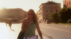 Stock Video Footage of Woman walking in the city and talking on loudspeaker, steadycam shot