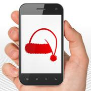 Stock Illustration of Entertainment, concept: Hand Holding Smartphone with Christmas Hat on display