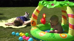 Stock Video Footage of Careless mother lay on plaid and baby splash water in kiddie pool. 4K