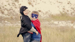Two boys  dressed as superheroes playing in the park outdoors Stock Footage