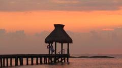 Woman walks along dock during sunset at tropical resort Stock Footage