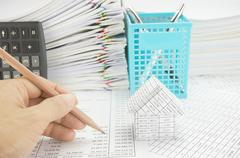 Man holding pencil for audit with house - stock photo