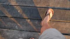 Looking down at feet in sandals walking on pier Stock Footage