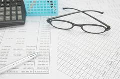 Silver pen have spectacles and calculator with blue pencil basket - stock photo