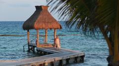 Woman walks down pier at tropical resort Stock Footage