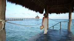 Woman standing on pier at tropical resort Stock Footage