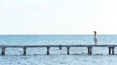 Woman walks down pier at tropical resort Stock Footage