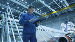 Aircraft maintenance mechanic is using tablet and greeting his colleague Stock Footage