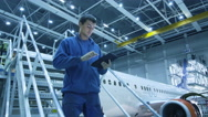 Stock Video Footage of Aircraft maintenance mechanic is using tablet and greeting his colleague