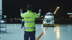 Aircraft marshal directs an airplane in the night to move towards hangar Stock Footage
