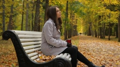 Portrait of a pretty woman with thermos cup sitting on a bench in autumn park. Stock Footage