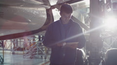 Aircraft maintenance mechanic uses tablet to inspect plane fuselage in a hangar Stock Footage