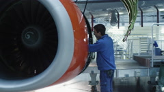 Aircraft maintenance mechanic with a flash light inspects plane engine Stock Footage