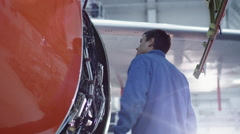 Aircraft maintenance mechanic inspects and tunes plane engine in a hangar - stock footage