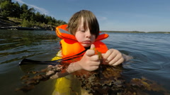 Boy floating in Baltic sea popping seaweed - Stockholm archipelago - stock footage