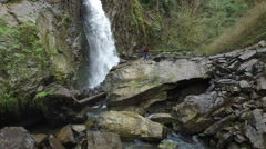 Aerial shot of backpacker taking photos of waterfall Stock Footage