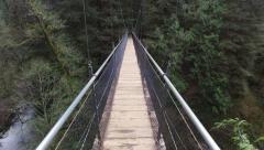 POV shot, walking across suspension bridge - stock footage