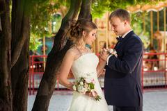 Couple holding each other near carousel - stock photo