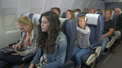 Disruptive child on plane shakes the seat of the woman in front - stock footage