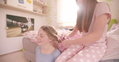 Adolescent girls in a bedroom doing each other's hair - stock footage