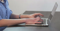 A young woman types on a silver laptop at a sleek, modern desk. - stock footage